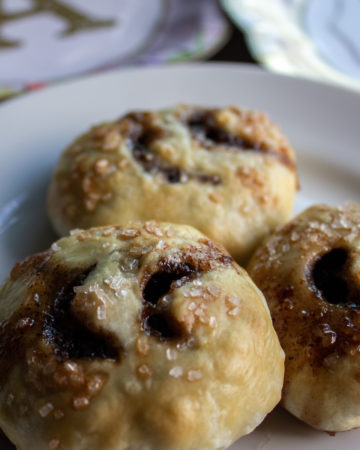 Baked Eccles Cakes, three, on a white plate.