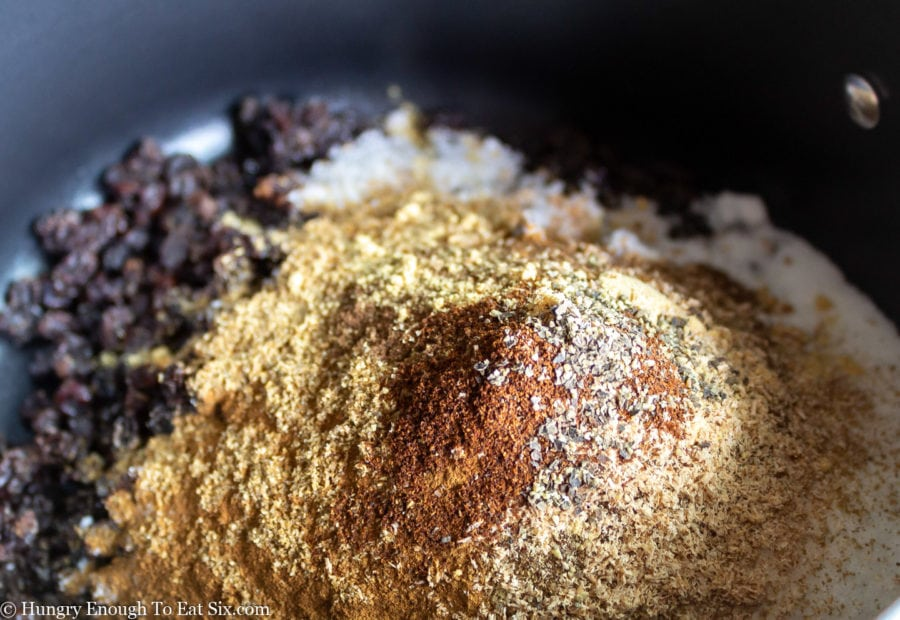 Mixed spice blend over sugar and currants in a pan.