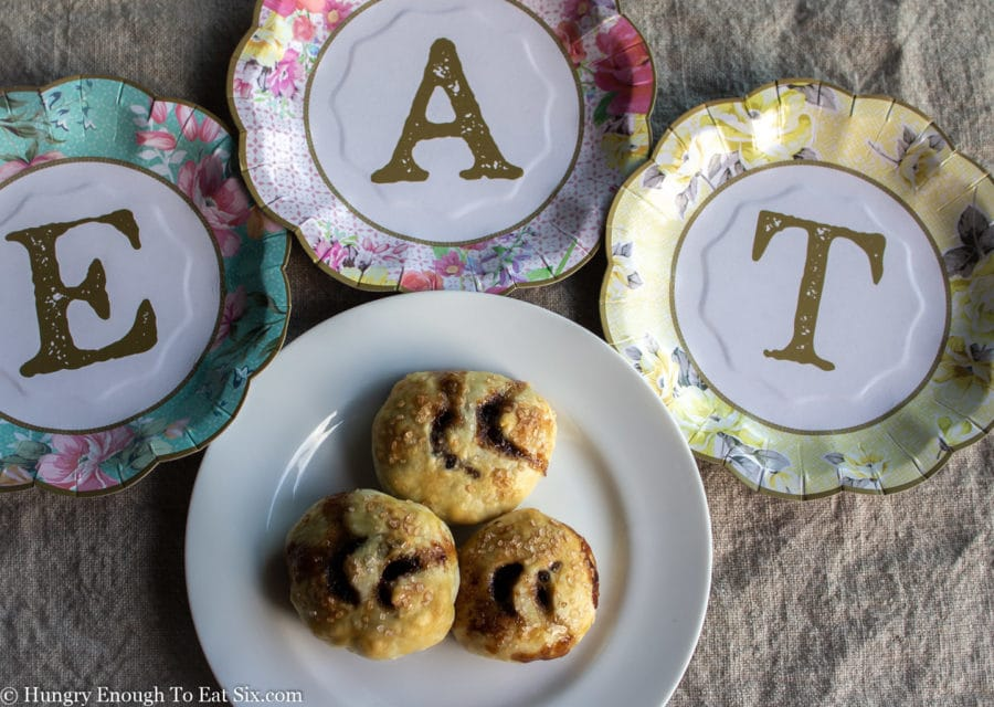 The word EAT above a white plate holding Eccles Cakes.