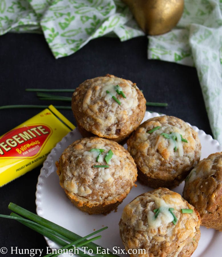 White plate holding five Vegemite muffins topped with cheese and diced chives.
