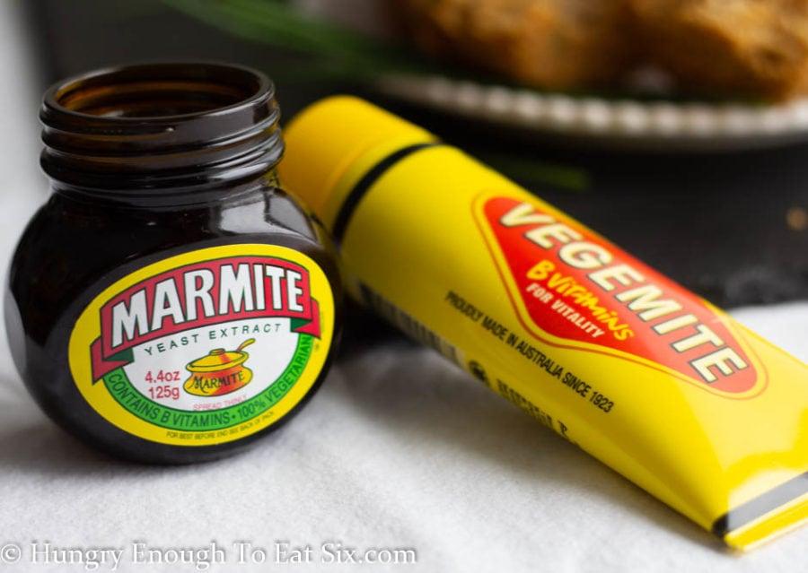 Jar of Marmite spread next to a tube of Vegemite spread.