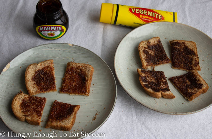 Two gray plates holding squares of toast spread with Vegemite and with Marmite.