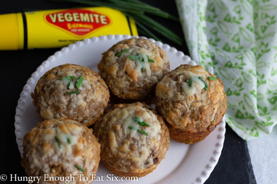 Five vegemite and cheese muffins topped with diced chives on a white plate, with a tube of vegemite behind.