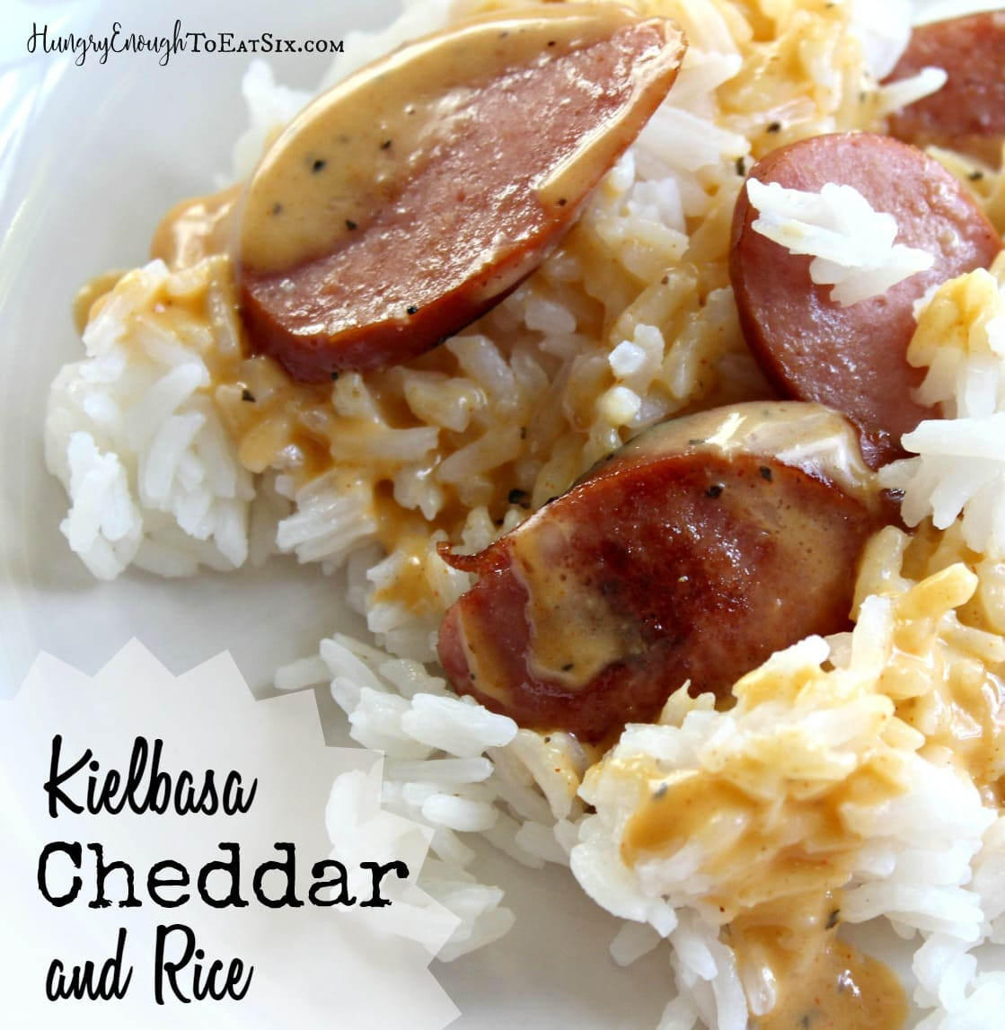 Image of Kiebasa, Cheddar sauce and rice recipe on a white plate