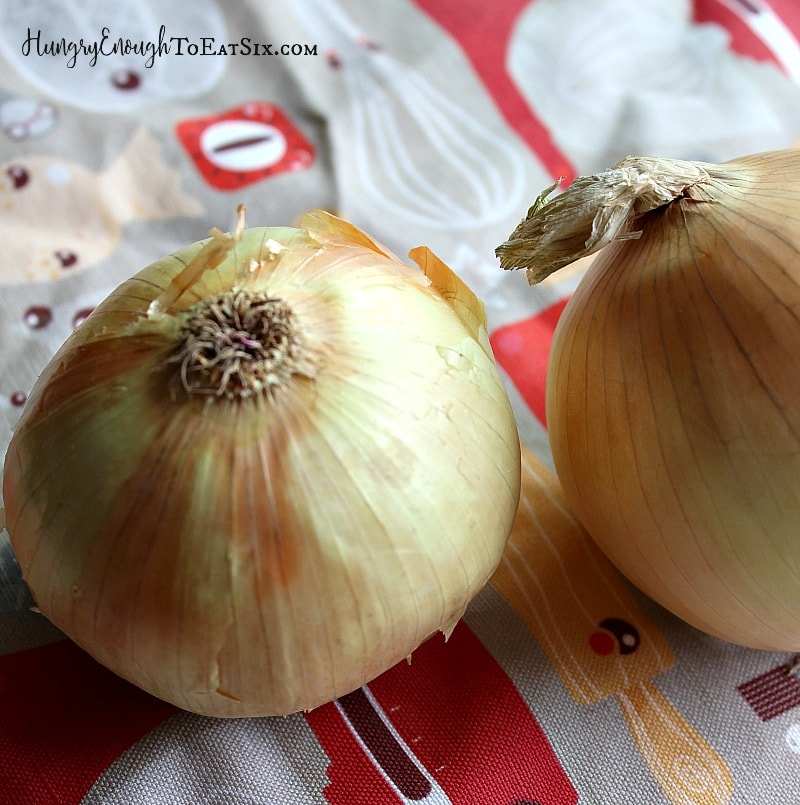 Two whole onions on a patterned cloth.