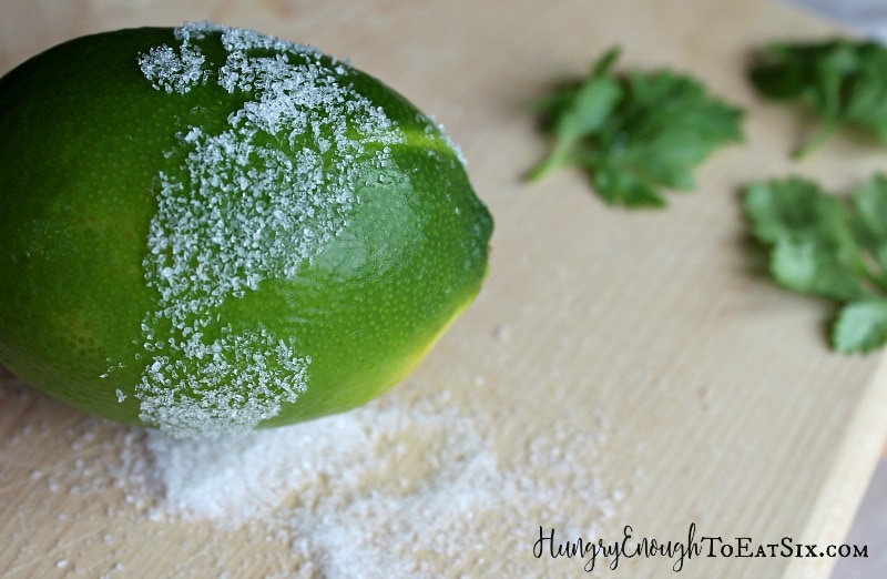 A green lime with salt on the outside and underneath, cilantro leaves in the background.