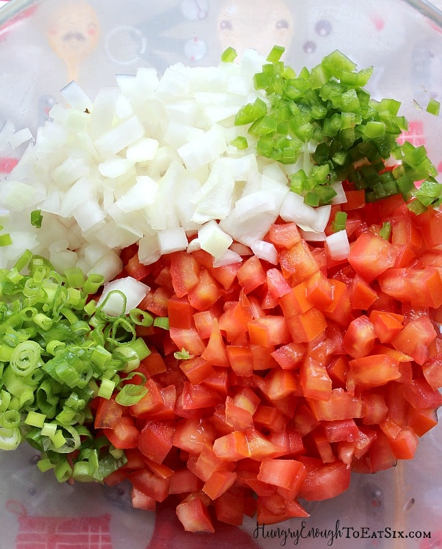 In a clear bowl freshly chopped onion, tomato, green onions and jalapeno pepper.