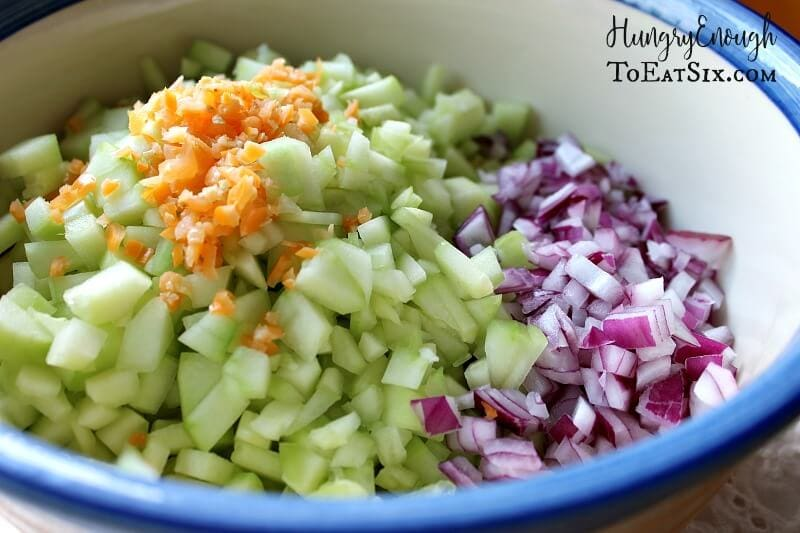 A bowl holding diced cucumbers, red onion and habanero pepper.