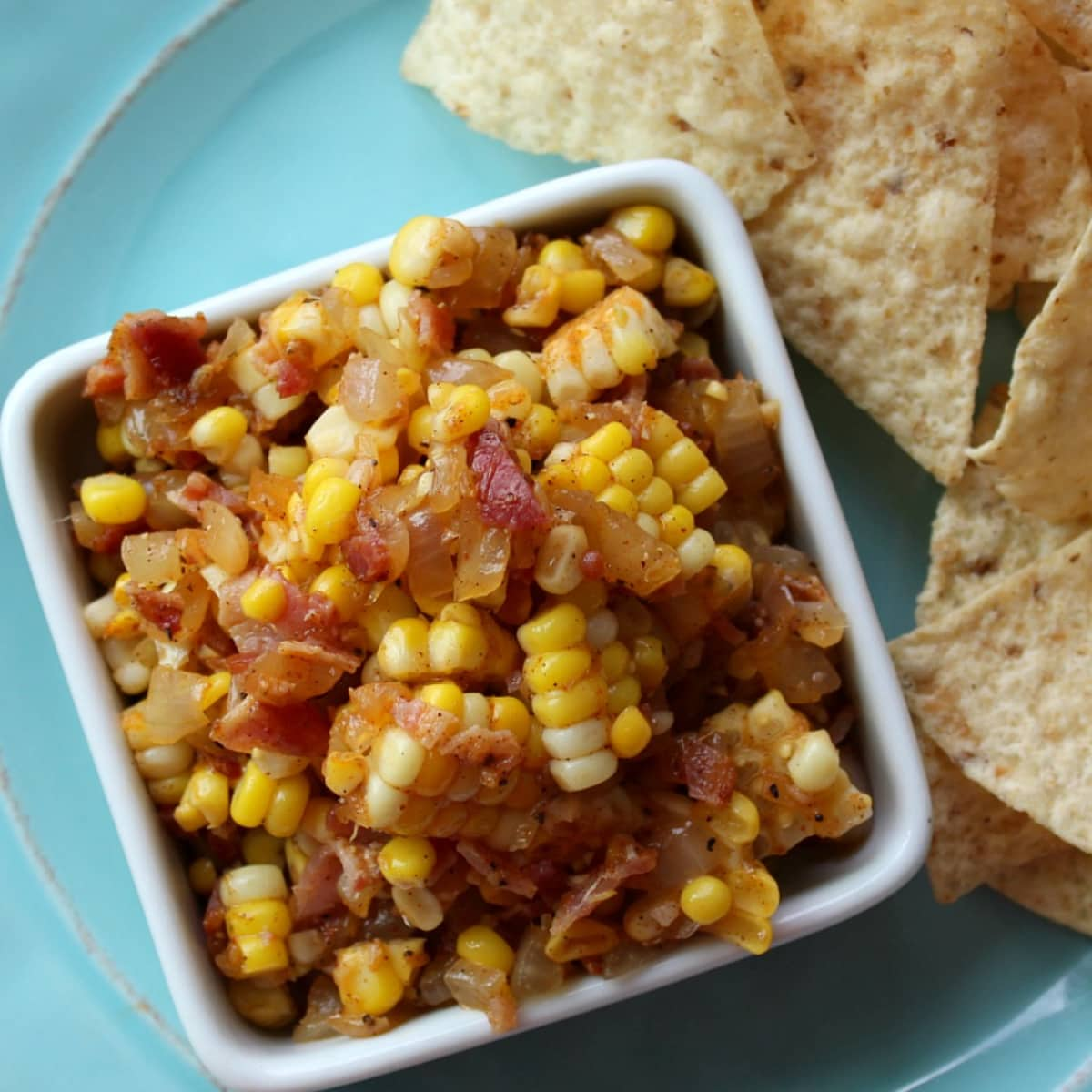 Blue plate holding white dish of corn salsa
