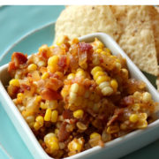 Corn and bacon salsa in a white dish next to chips