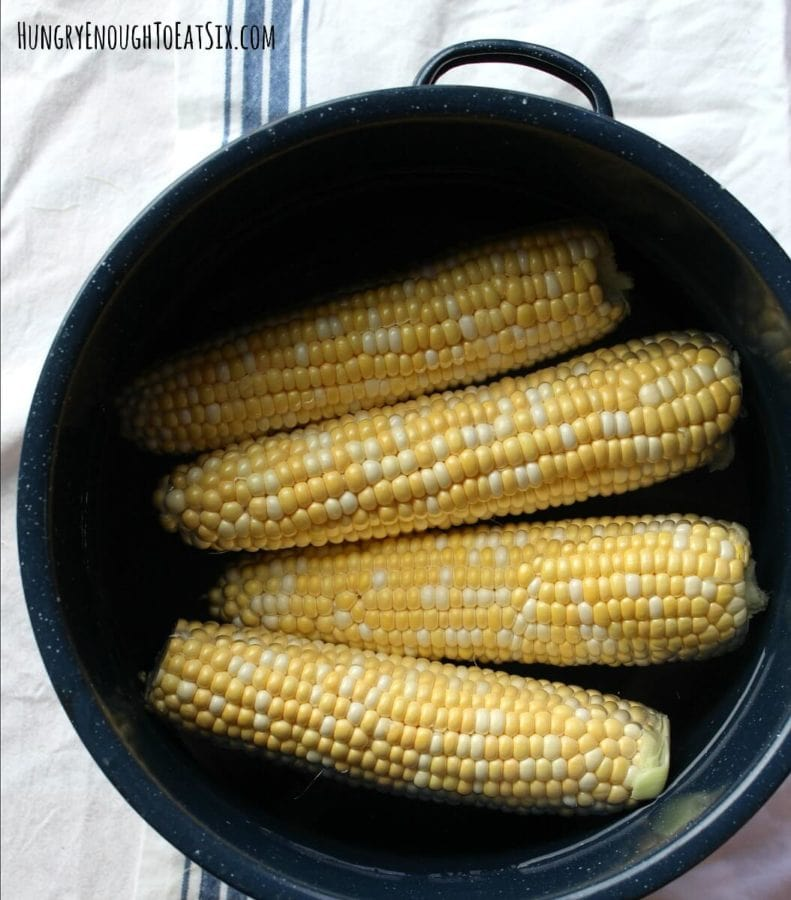 Image of 4 ears of corn in a stock pot under water.