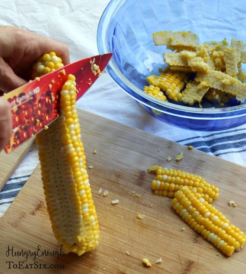 Image of a knife slicing corn kernels off of a cob.