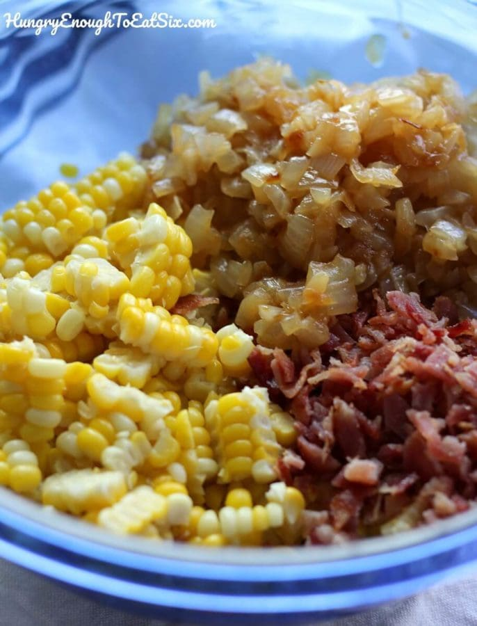 Image of mixing bowl holding corn kernels, bacon, and cooked onions.