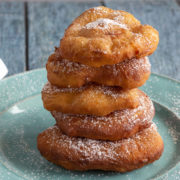Five fried bread dough pieces stacked on a plate