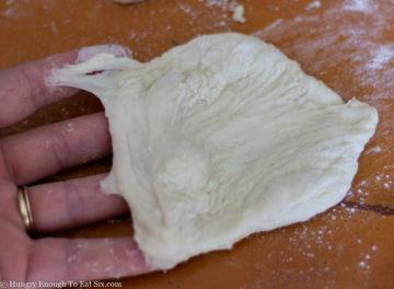 Piece of bread dough stretched over fingers.