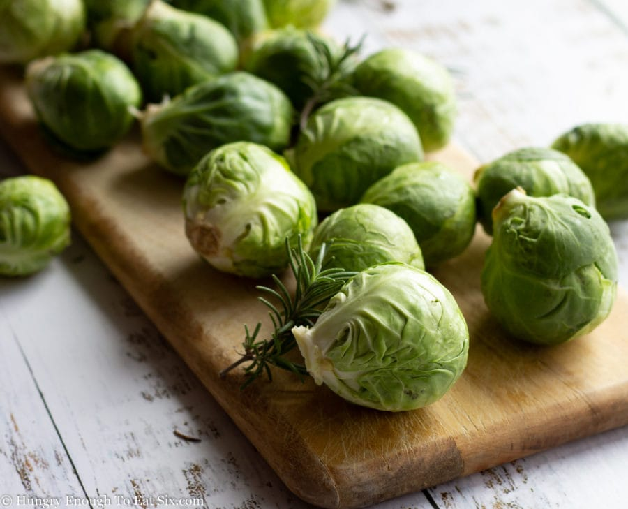 Whole Brussels sprouts laying on a cutting board.