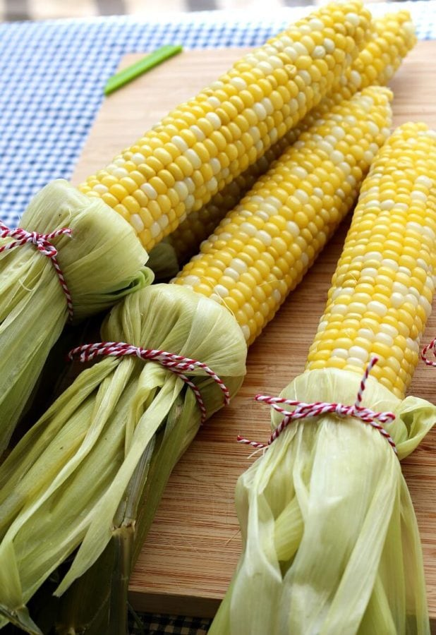 Ears of cooked corn with husks pulled back and tied below with kitchen string.