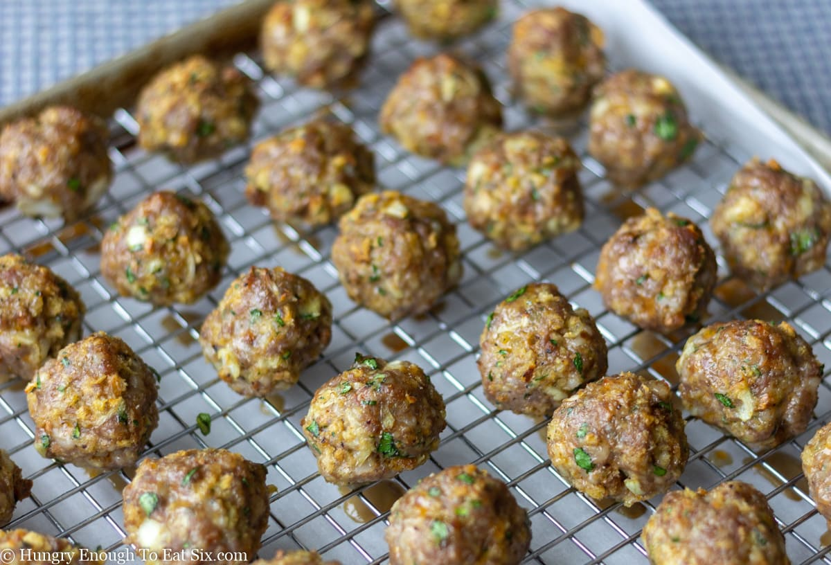 Rows of baked meatballs on a wire cooling rack