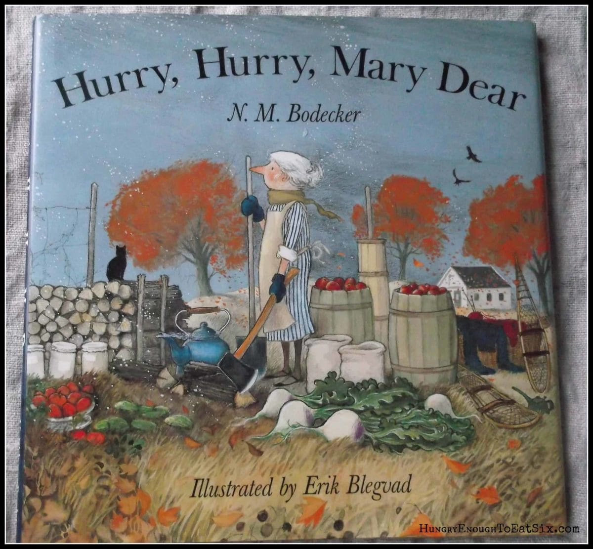 Children's book cover with fall trees, apples, and an old woman
