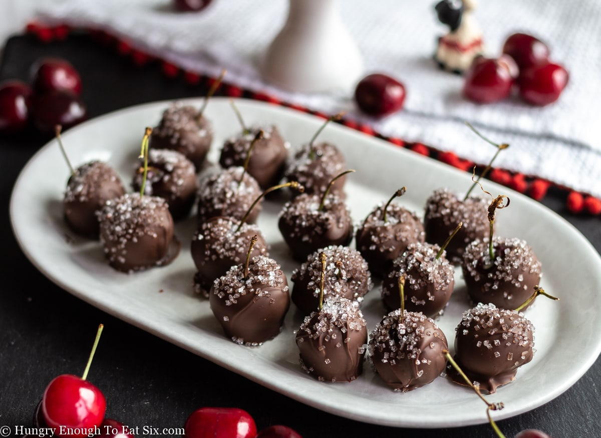 White platter of chocolate and sugar decorated cherries by a white cloth.