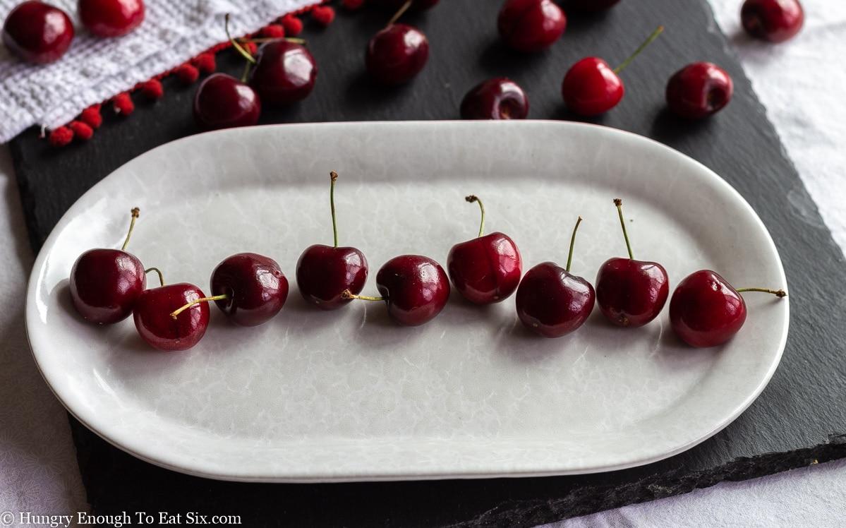 Dark red cherries in a line on an oblong white platter.