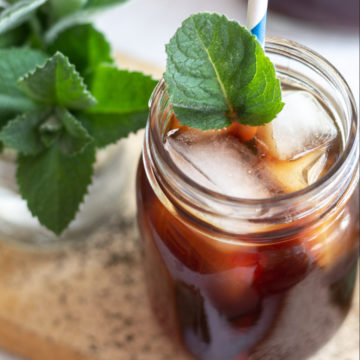 Glass jar with dark iced tea, ice cubes and fresh bright green mint leaves.