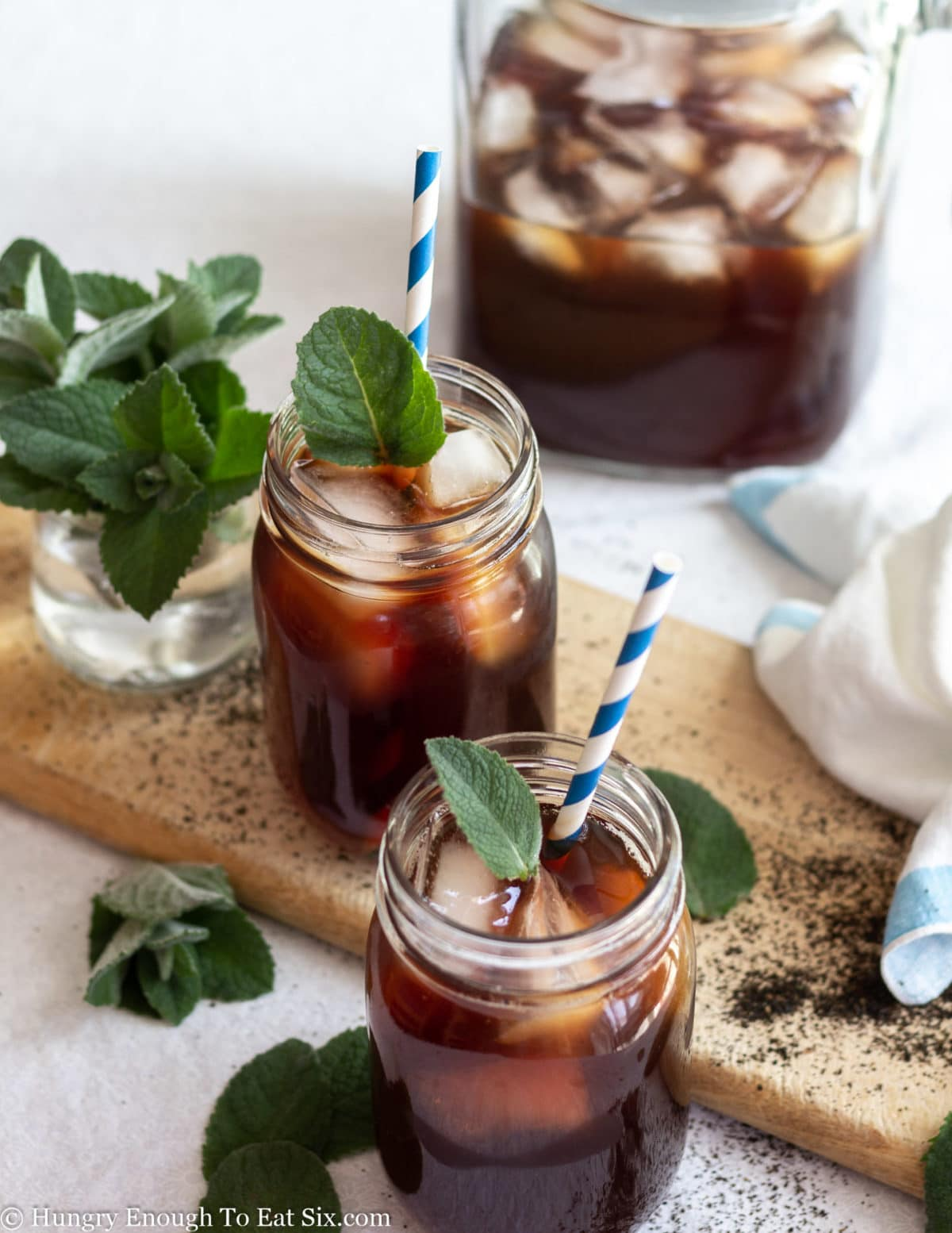 Pitcher and mason jars of dark iced tea with ice cubes and mint leaves.