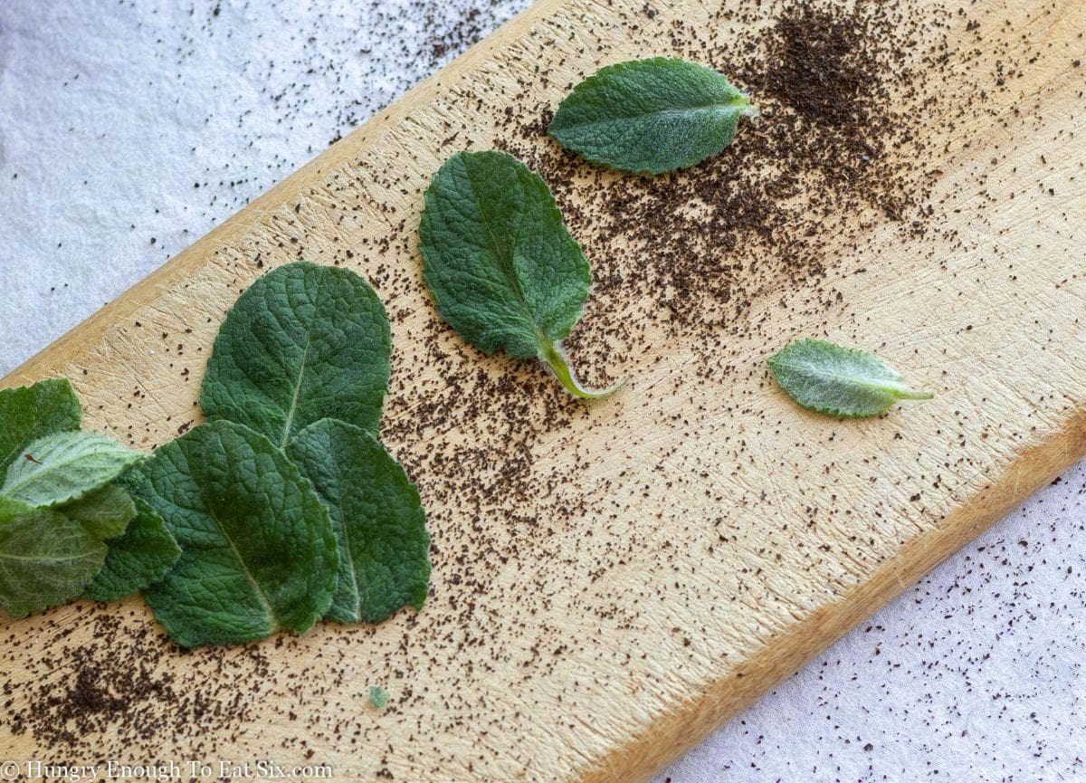 Spearmint leaves and loose tea scattered over a long wooden cutting board.