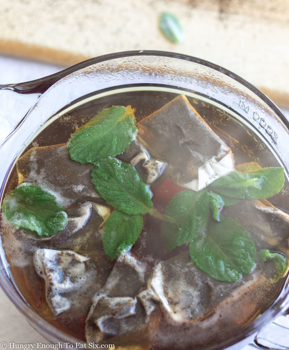 Several tea bags and mint leaves steeping in a Pyrex bowl of boiling hot water.