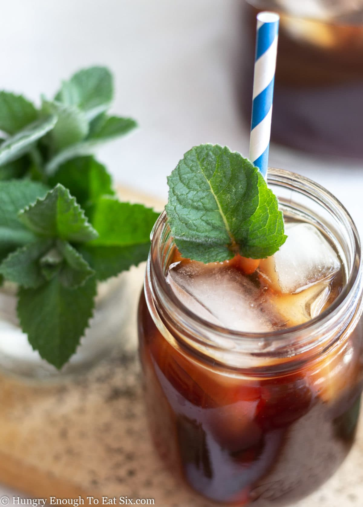 Mint leaf garnish on a mason glass jar of iced tea.