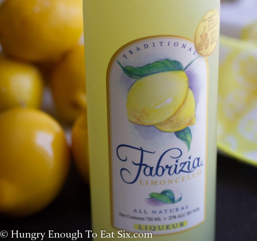 Bottle of limoncello liqueur with lemons behind.