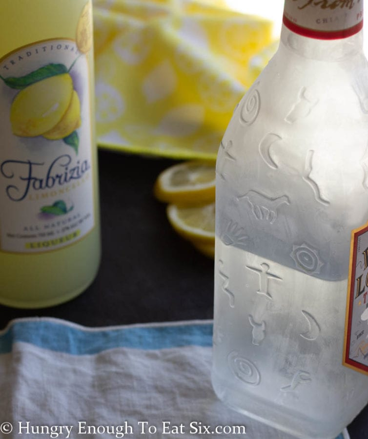 Chilled bottles of limoncello and tequila on a blue and white cloth
