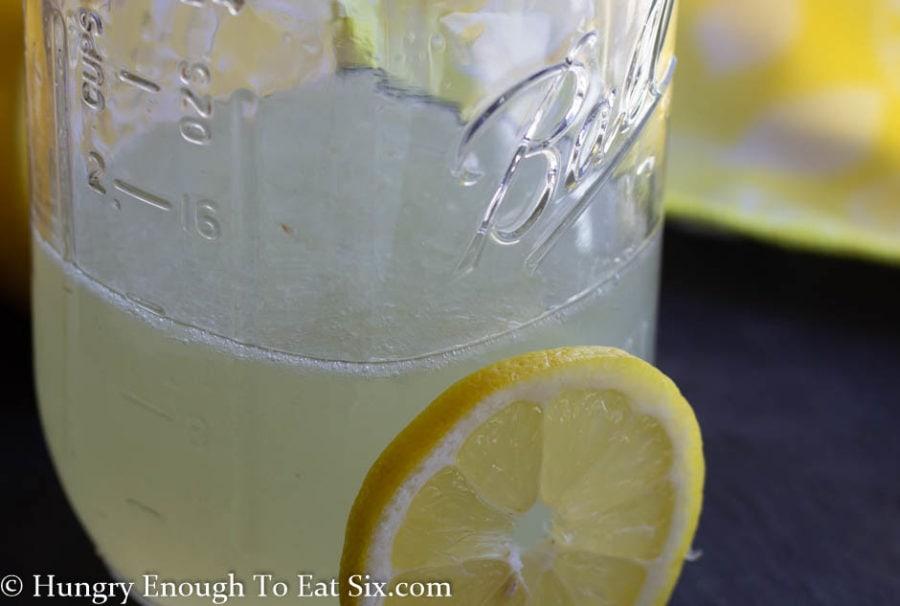 Tall mason jar with lemon margarita mix, slice of lemon next to it