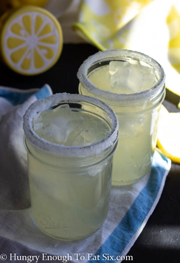 Vertical shot of small mason jars filled with lemon margarita mix and ice.