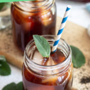 Glass mason jar with iced tea, ice cubes and a mint leaf.