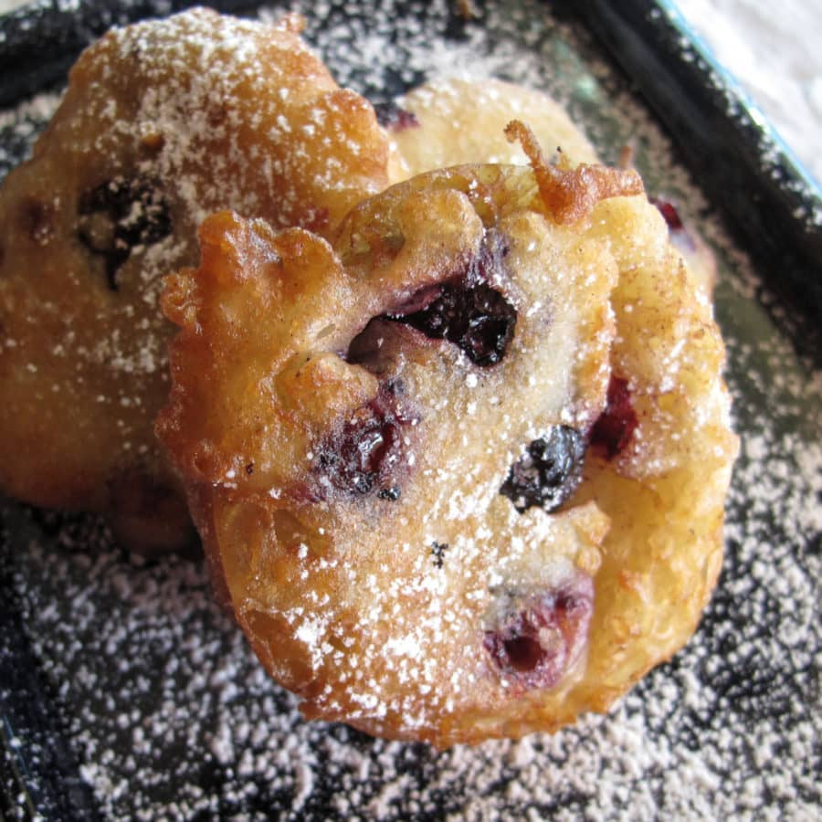Blueberry fritters on a black plate.