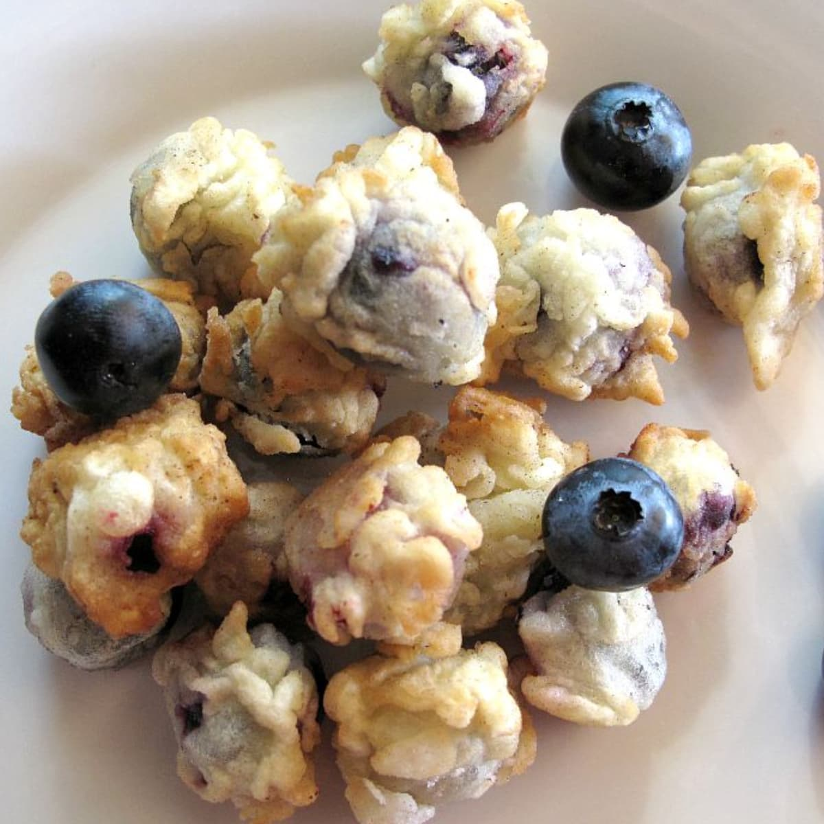 Deep fried blueberries with a few fresh blueberries