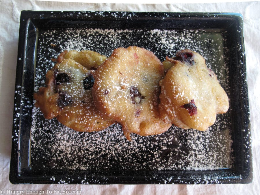 Three fried blueberry fritters dusted with confectioner's sugar.