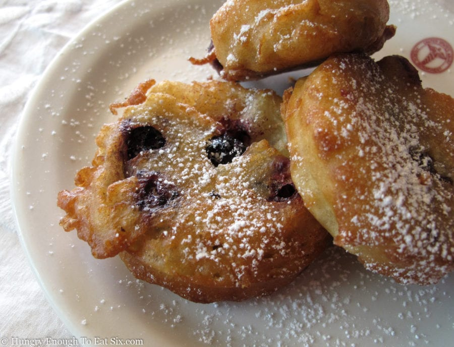 Blueberry fritters on a plate dusted with sugar.