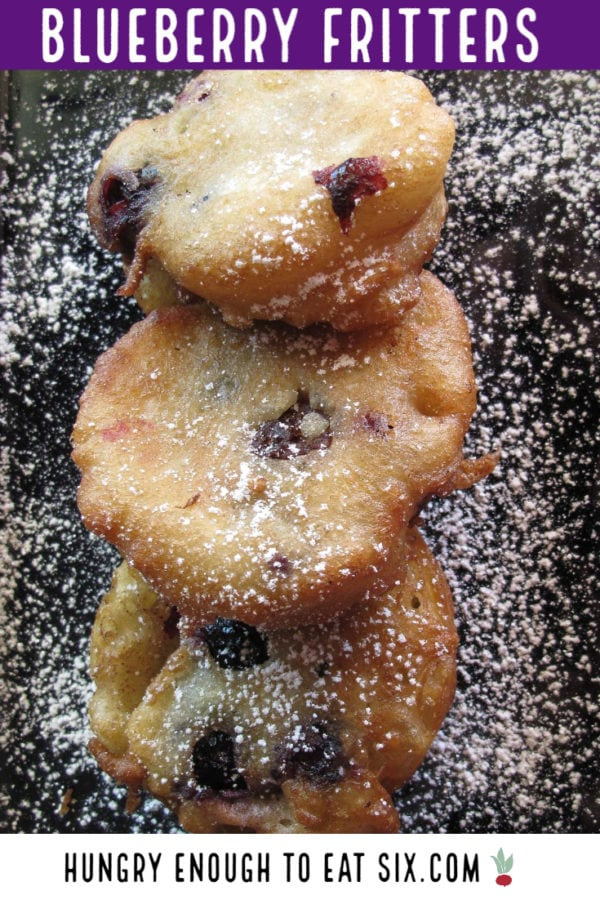 Fritters with blueberries and confectioner's sugar.