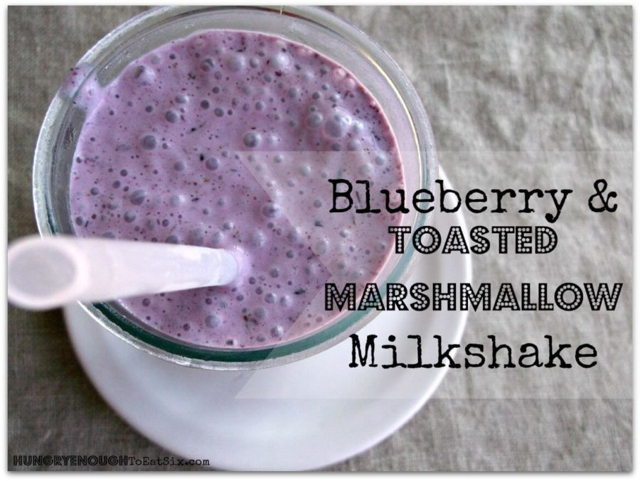Blueberry & toasted marshmallow milkshake in a glass with a straw.