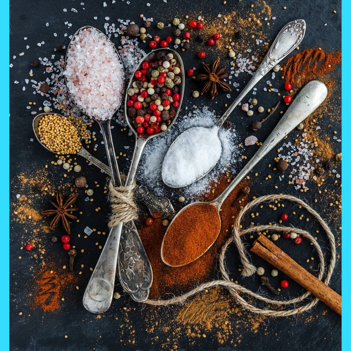 Spices in teaspoons and scattered on a dark board