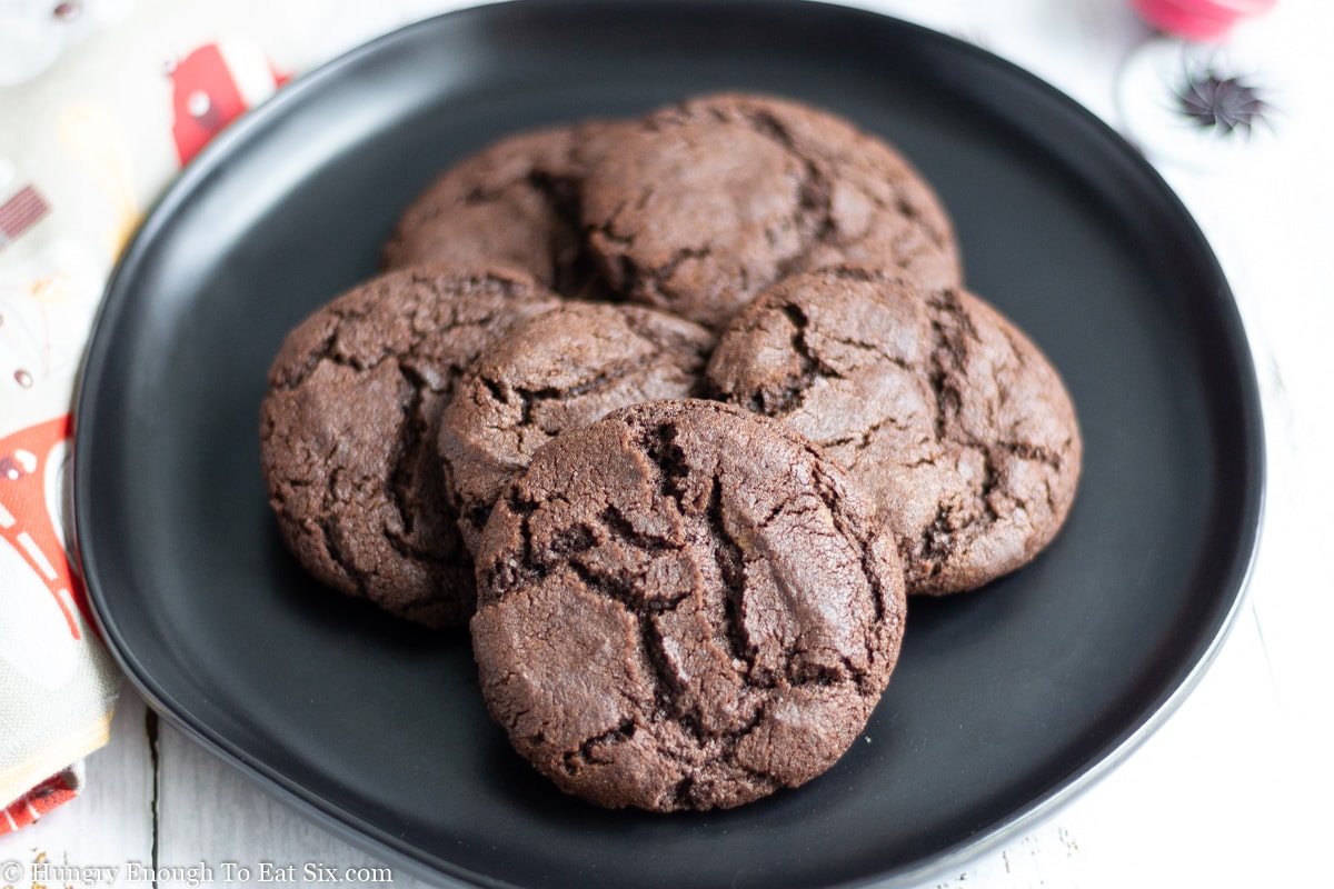 Chocolate crinkled cookies on a black saucer