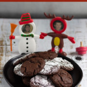 Chocolate and sugar dusted cookies on a black plate on a wood surface