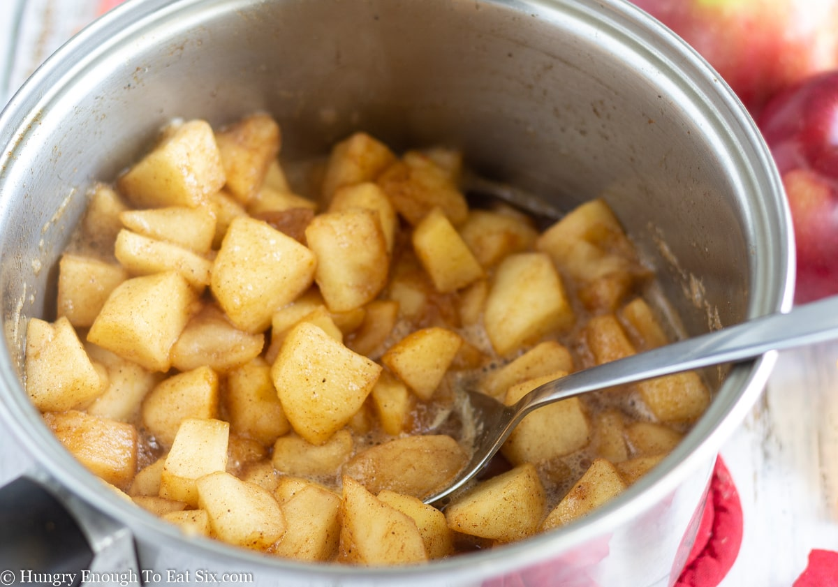Cooked apple chunks in a pan with a spoon