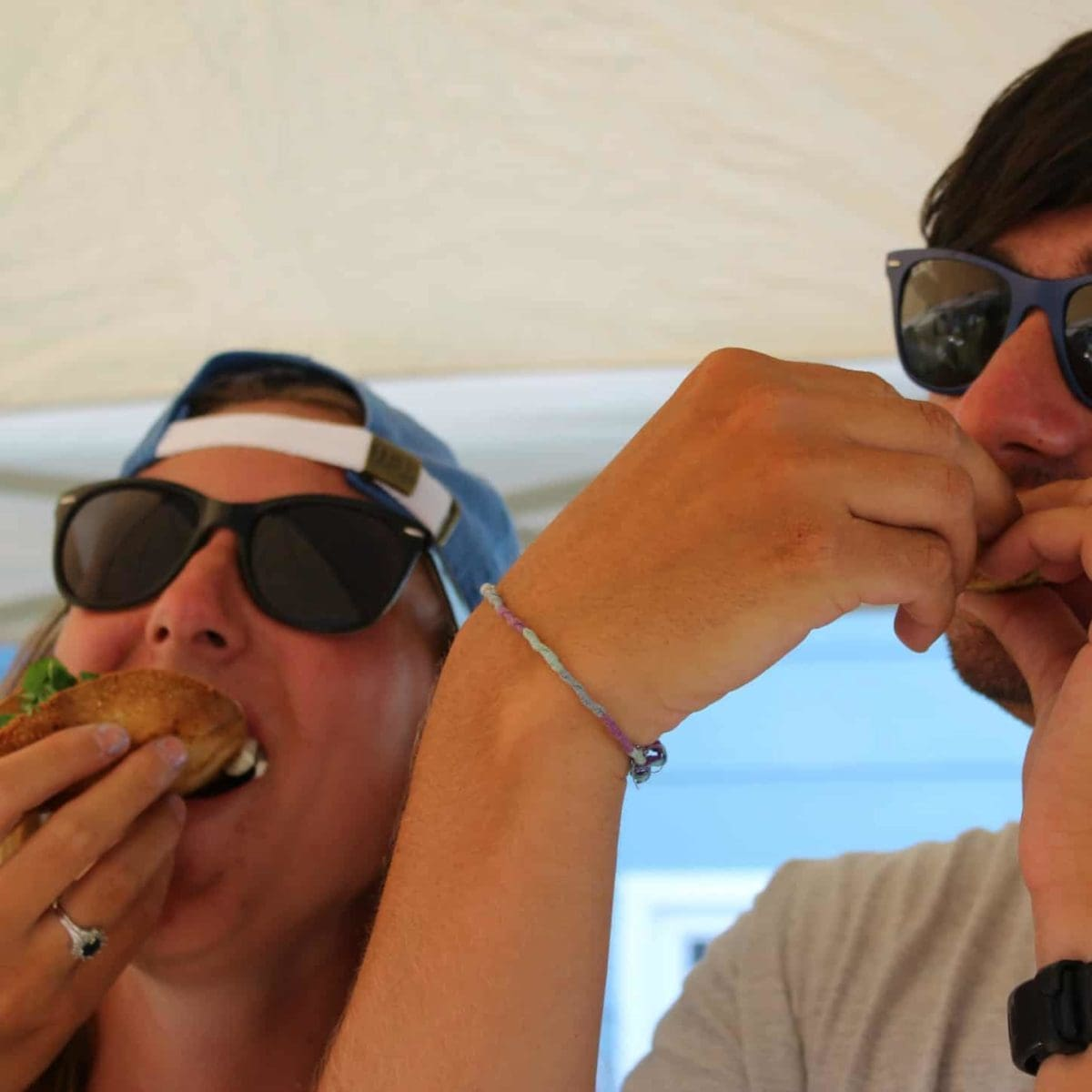 Man and woman with sunglasses eating tacos.