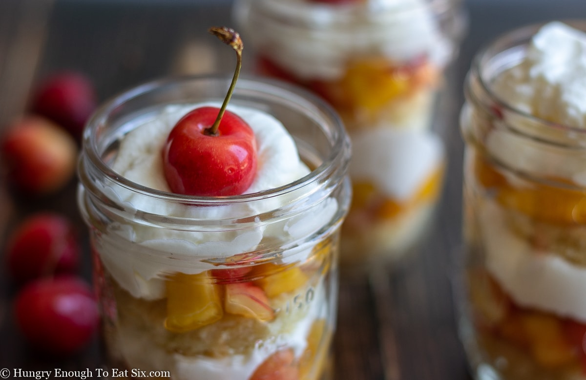 A cherry-topped trifle in a small glass mason jar.