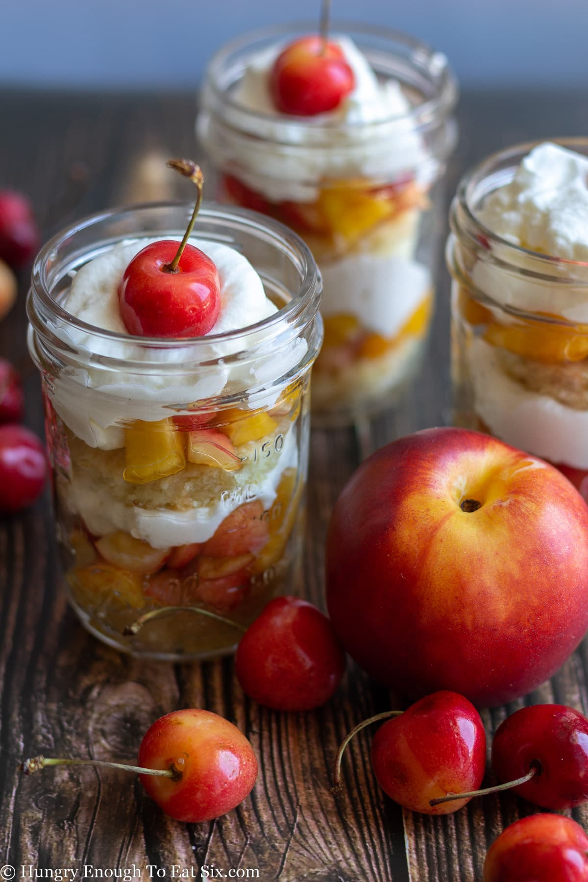 Whole nectarine and cherries next to a glass jar holding a fruit and cream trifle.
