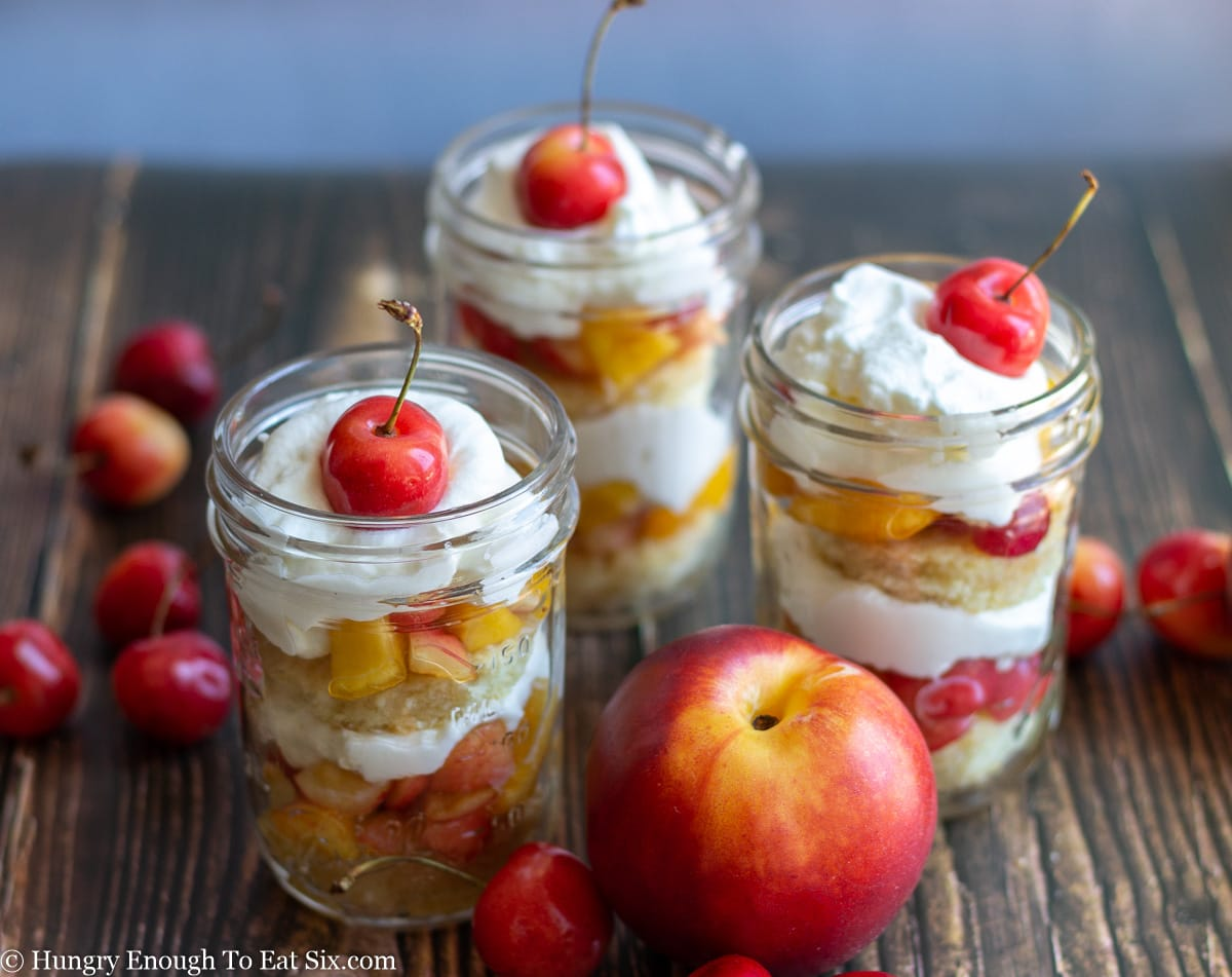 Three fruit and cream trifles in glass jars with fruit scattered around.