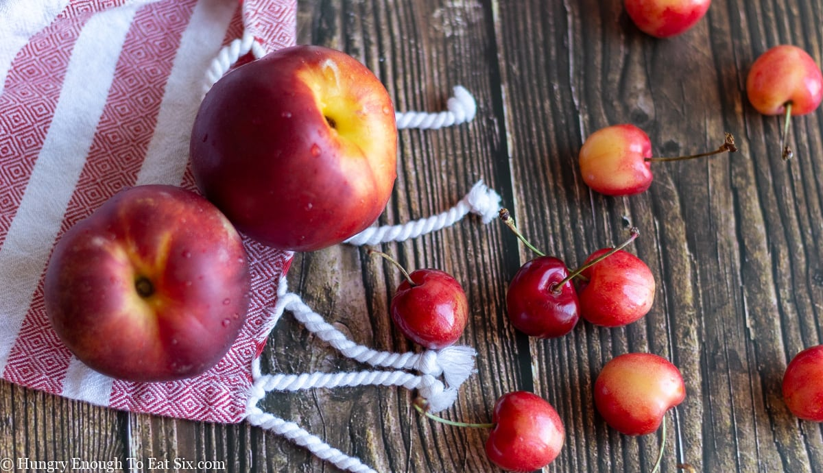 Nectarines and cherries on a wood surface and red cloth.
